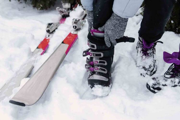 Woman putting on ski boots