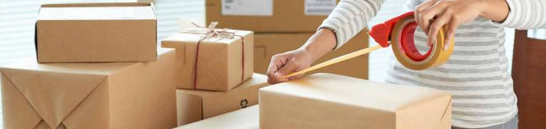 Woman packing up shipping boxes