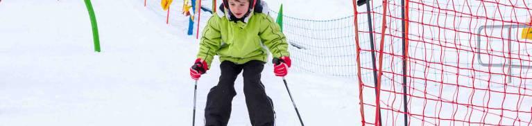 Little kid enjoying skiing in ski school